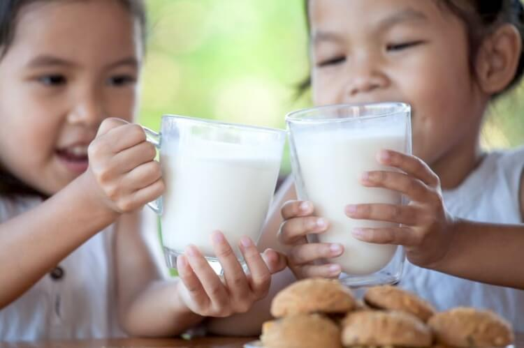 two girls with milk and cookies