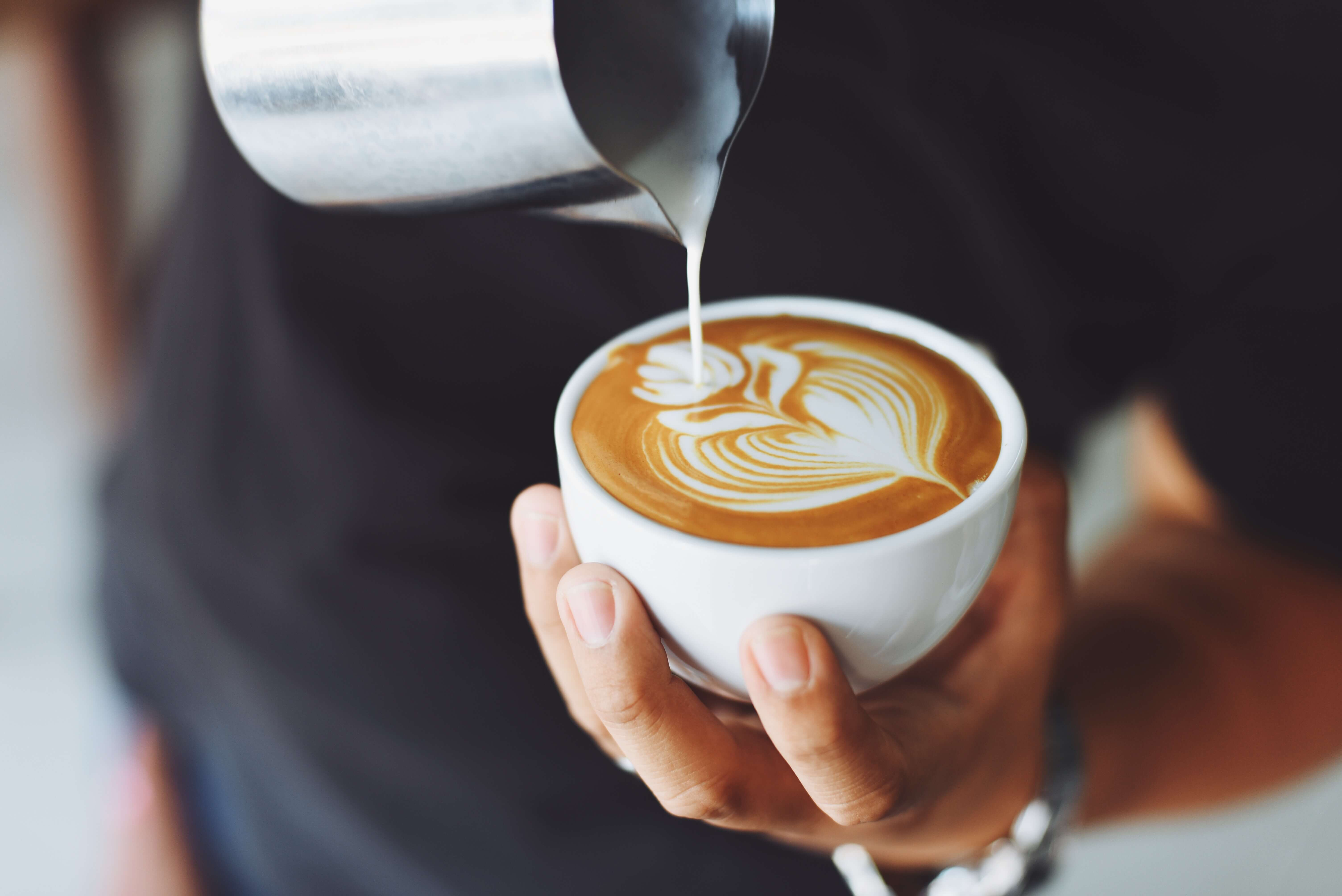 man pouring milk into coffee cup